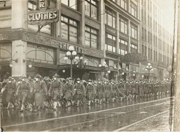 39. peší pluk v roku 1918 pochodoval centrom Seattlu v maskách oblečený na ceste k nasadeniu do Francúzska. (Národný archív)